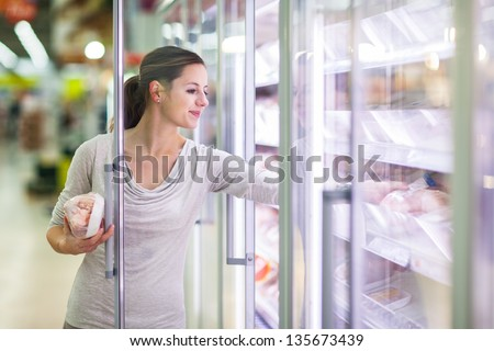 Young woman shopping for meat in a grocery store (color toned image) - stock photo