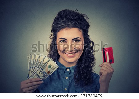 Young woman shopping holding showing credit card and cash dollar banknotes bills  - stock photo