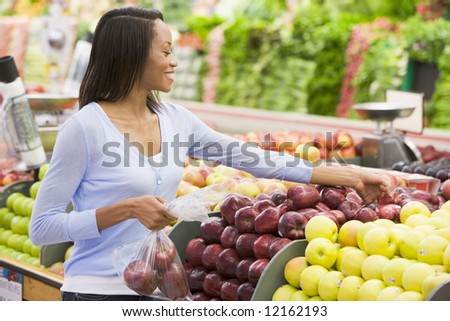 Young woman shopping in produce section of supermarket - stock photo