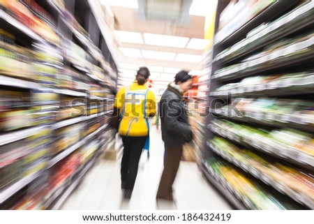 Young woman shopping in the supermarket,motion blur - stock photo