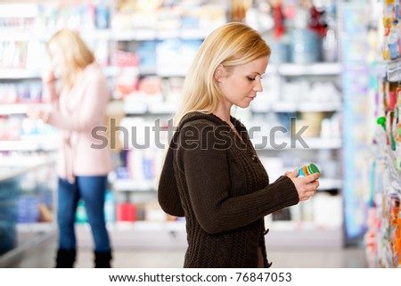 Young woman shopping in the supermarket with people in the background - stock photo