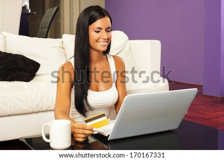 Young woman shopping online with credit card. Selective focus on face - stock photo