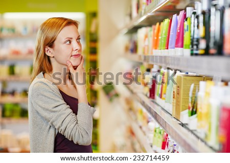 Young woman shopping selective and sustainable in a supermarket - stock photo