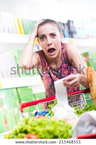 Young woman shouting and checking a long receipt at supermarket. - stock photo