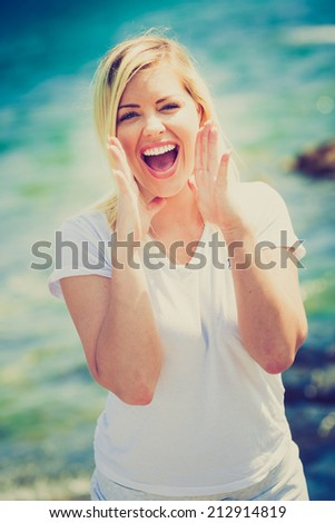 Young Woman shouting on the beach, vivid colors - stock photo
