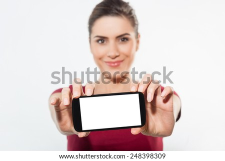 Young woman show display of mobile cell phone with white screen and smiling on a white background. Focus on hand with mobile phone - stock photo