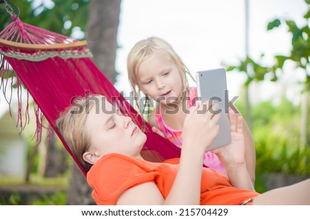 Young woman show pictures to adorable daughter on electronic tablet reader relaxing in hammock under palm trees