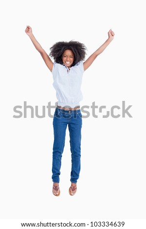 Young woman showing a beaming smile while raising her arms above the head - stock photo
