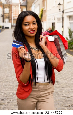 young woman showing a credit card holding shopping bags - stock photo