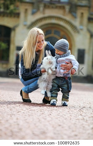 Young woman showing a fancy rabbit to her son - stock photo