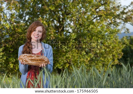 Young woman showing a freshly baked bread in a corn field
