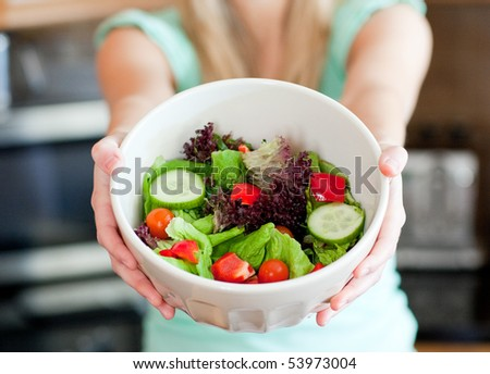Young woman showing a salad in the kitchen - stock photo