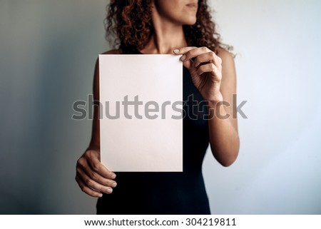 young woman showing a white blank page of clipboard on a white background - stock photo