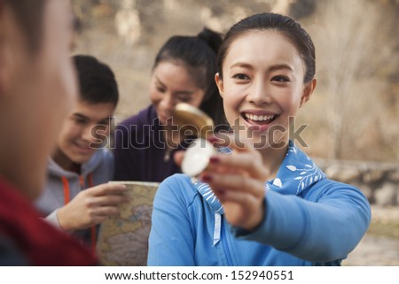 Young woman showing compass to her friend - stock photo
