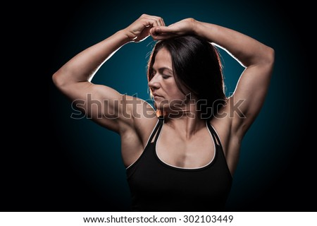Young woman showing her muscles - stock photo