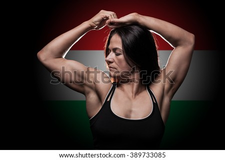 Young woman showing her muscles - with the Hungarian flag in the background - stock photo