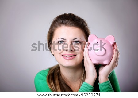 Young woman showing her pink piggy bank - stock photo