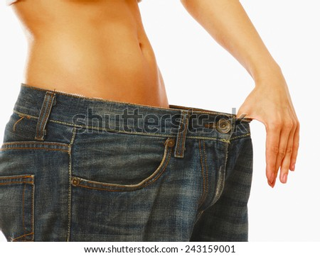 Young woman showing how much weight she lost isolated on white background. Focus on belly - stock photo