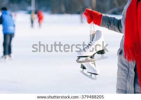 Young woman showing ice skates for winter