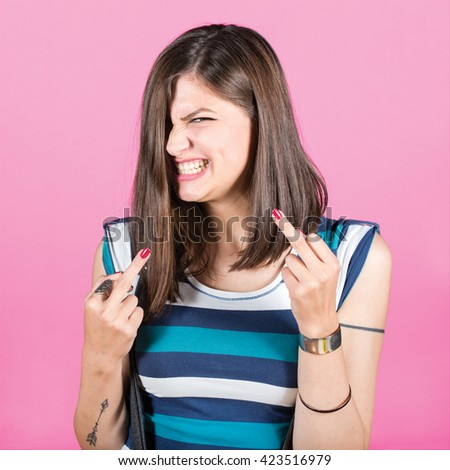 Young woman showing middle fingers against pink background