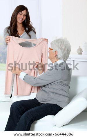Young woman showing new clothes to grandmother - stock photo
