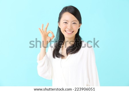 young woman showing OK gesture against blue background - stock photo