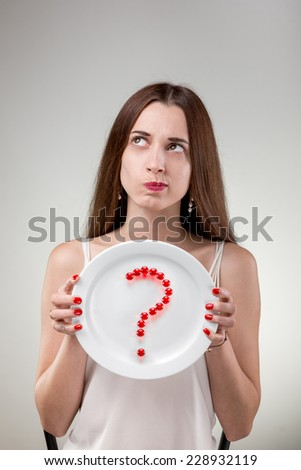 Young woman showing plate with vitamins pills set out question mark in studio on white background - stock photo