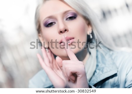 Young woman showing quiet sign. Outdoors portrait. - stock photo