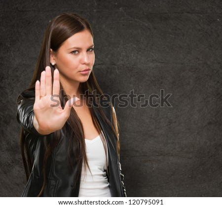 Young Woman Showing Stop Hand Gesture against a grunge background - stock photo