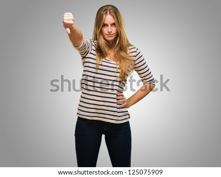 Young Woman Showing Thumb Down Sign against a grey background - stock photo