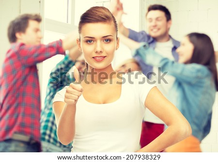 young woman showing thumbs up at school - stock photo
