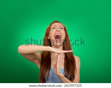 Young woman showing time out hand gesture, frustrated screaming to stop isolated on green background. Too many things to do. Human emotions face expression reaction - stock photo