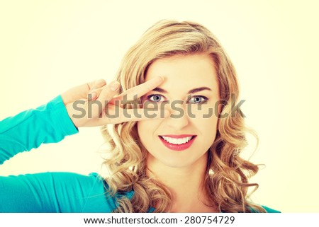 Young woman showing two fingers,victory sign, positive or peace gesture - stock photo