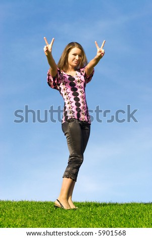 Young woman showing victory sign. - stock photo