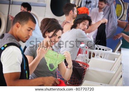 Young woman shows disinterested man her panties in a laundromat - stock photo