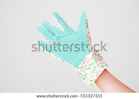 Young woman shows her palm in safety rubber dot coated colorful flower patterned gardening gloves