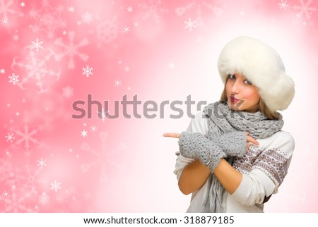 Young woman shows pointing gesture on red snowy background - stock photo