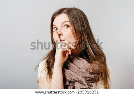 Young woman shows silence finger to his mouth. On a gray background. - stock photo