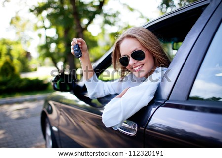 Young woman shows the keys to her new car - stock photo