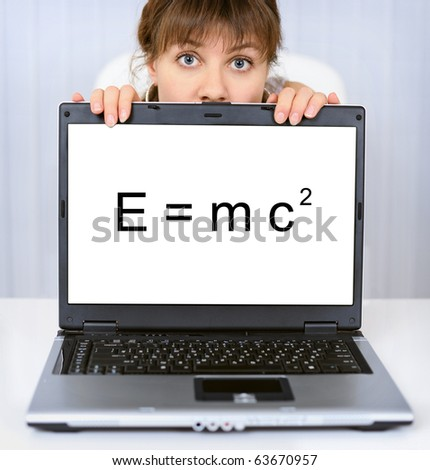 Young woman shows us a computer screen with formula