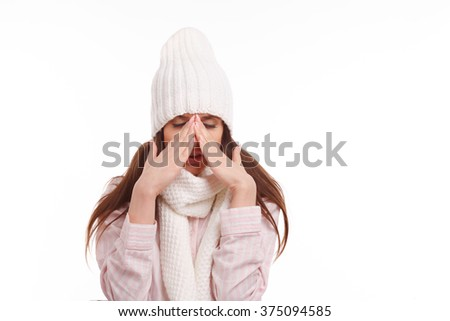 Young woman sick and closed with a scarf on white background. Sneezing into Tissue.