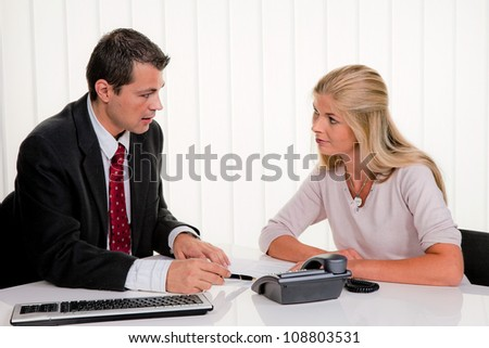 young woman signing a contract in an office - stock photo