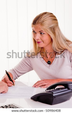 Young woman signs a contract in an office