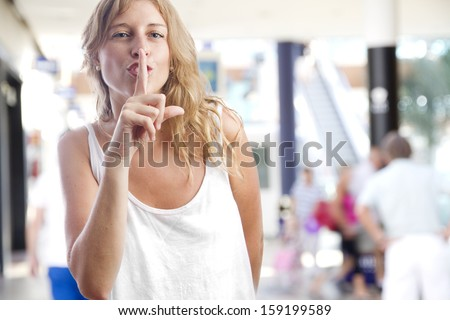 young woman silence gesture in a shopping center - stock photo