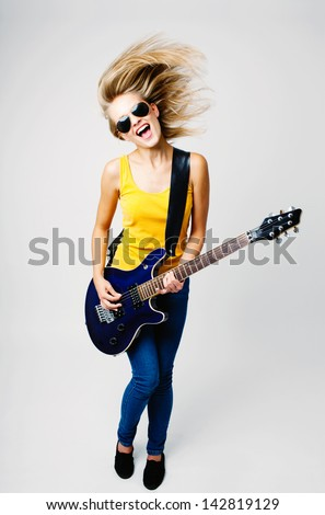 Young woman singing and playing on electric guitar - stock photo
