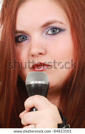 Young woman singing into a microphone - stock photo