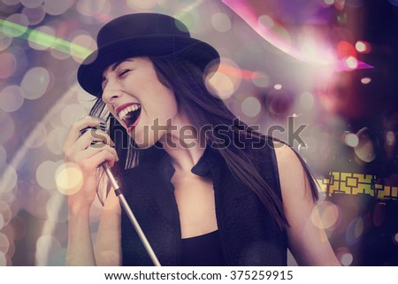 Young woman singing with the microphone - stock photo