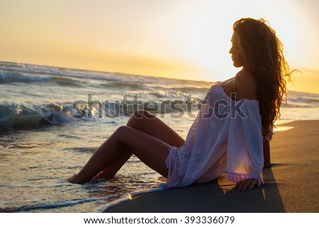 young woman sit at sand beach in long shirt enjoy in sunset bay the sea, side view full body shot - stock photo