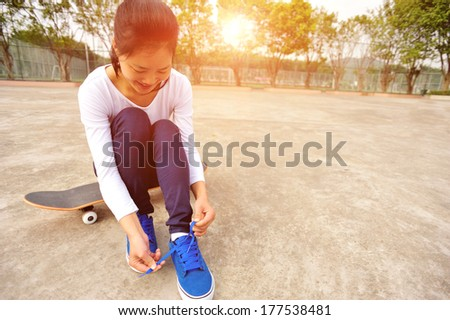 young woman sit on skateboard try new shoes - stock photo