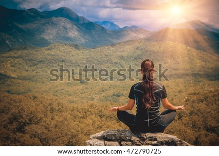 Young woman sits at peak of mountain in lotus pose, doing yoga and feel harmony of body and nature. Relax and meditation on outdoor. Healthy lifestyles, concept of body and soul. Vintage effect.